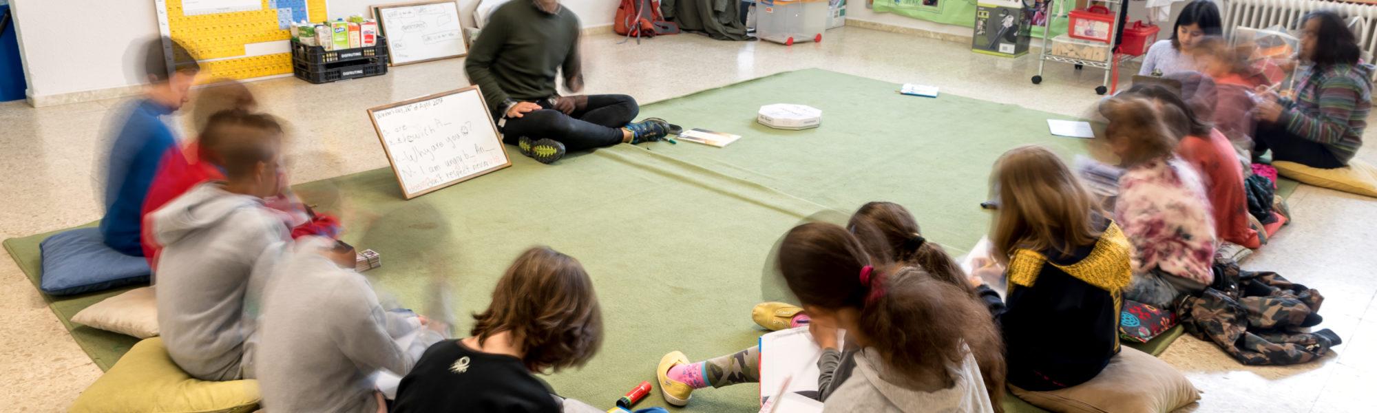 Aula amb nens asseguts en rotllana