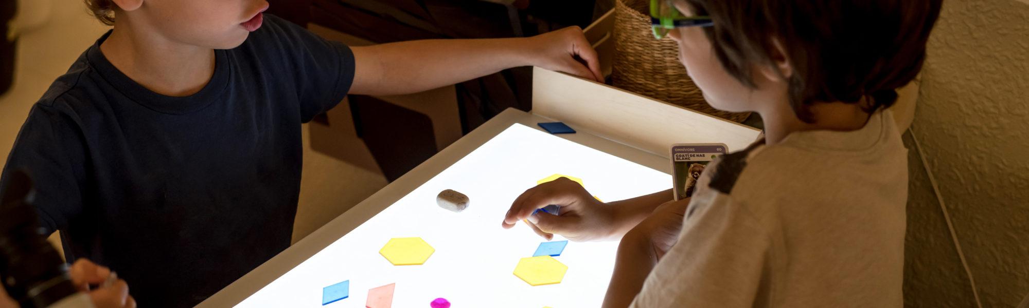 Nens jugant amb una taula de llum