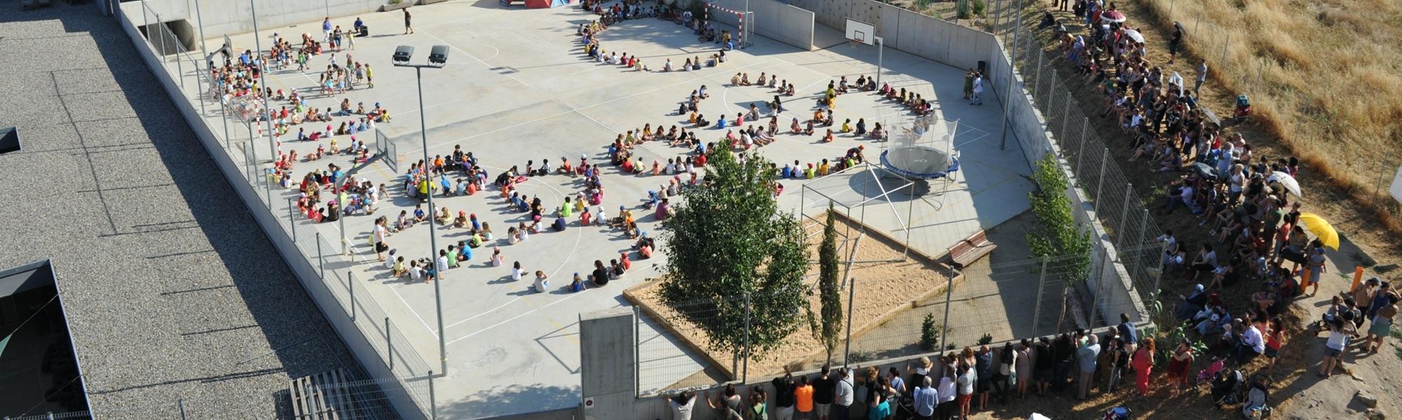 Escola Ítaca, vista aèria del pati on els alumnes fan grups en rotllanes asseguts a terra